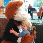 A young patient hugs the PSO's musical ambassador, Fiddlesticks, while PSO violist Penny Brill and cellist Gail Czajkowski play at an October 2013 CHP Atrium
