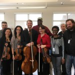 A PSO string quartet joins veterans and staff at the VA Pittsburgh's H.J. Heinz Campus for a photo after an April 2016 event.