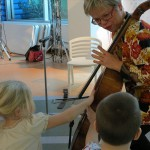 "The PSO's Principal Cello, Anne Martindale Williams, invites two young patients to touch her cello at CHP's January 2013 reading of the book ""Marvin Makes"
