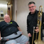 A veteran poses with the PSO's Principal Trombone, Peter Sullivan, after enjoying holiday music at the VA.