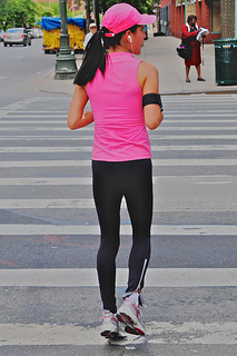 A woman runs while listening to headphones